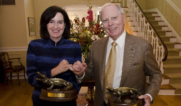 Crawford and Wallace fist bump while holding Alumni Leadership Awards