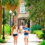Two students hold a discussion in front of a UF classroom building
