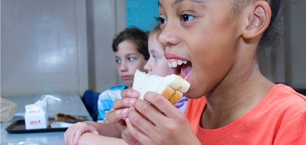Elementary school students eat peanut putter and jelly sandwiches