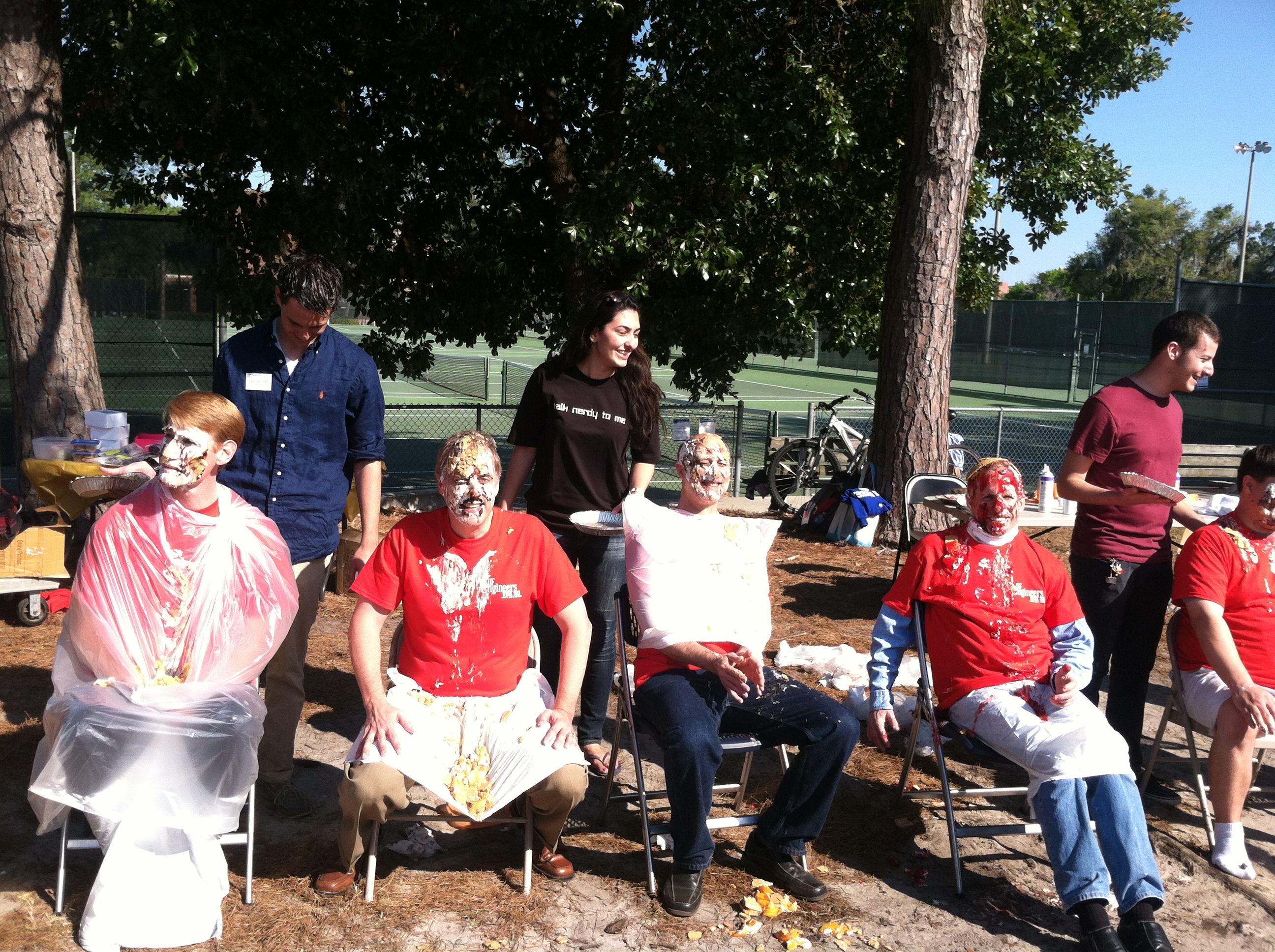 A group of faculty take a seat after being pied in the face