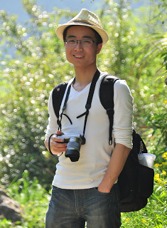 Dr. Kai Pan, camera in hand, poses for an outdoor photo