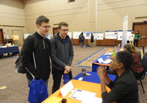 Two students receive information at a career fair booth